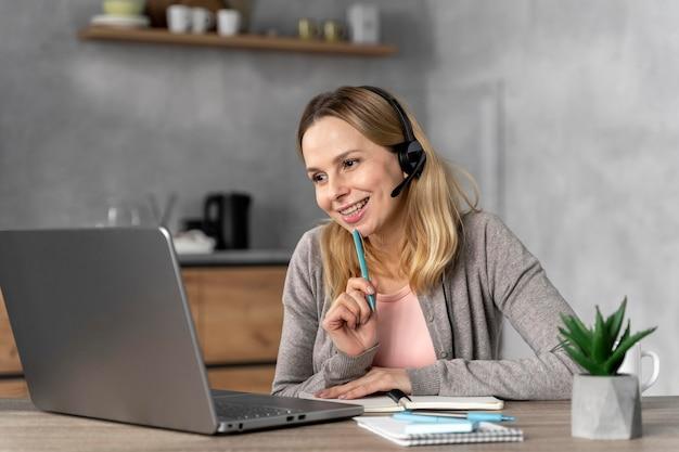 Femme avec casque travaillant sur ordinateur portable