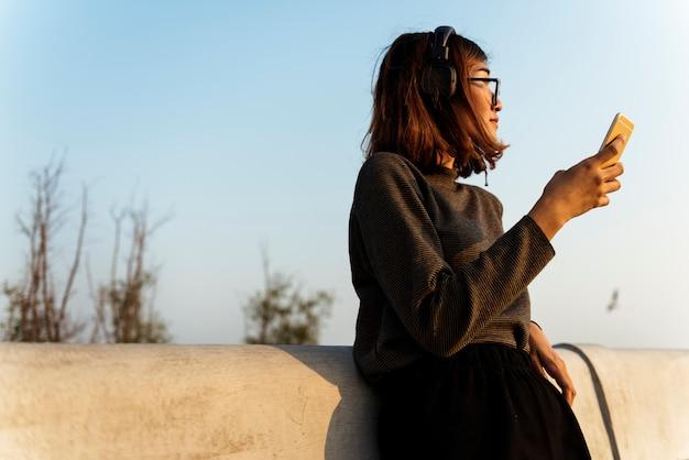 Femme avec des casques d'écoute de la musique sur téléphone mobile