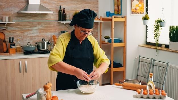 Une femme casse un œuf au-dessus de la farine pour faire de la pâte pour les produits de boulangerie. chef pâtissier âgé cassant des œufs sur un bol en verre pour une recette de gâteau dans la cuisine, mélangeant à la main, pétrissant les ingrédients préparant un gâteau fait maison