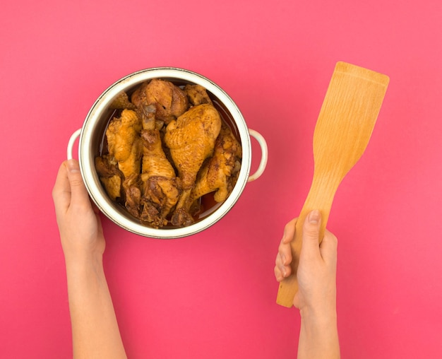 Femme avec une casserole remplie de poulet frit et d'une spatule en bois, fond plat rose, vue de dessus photo