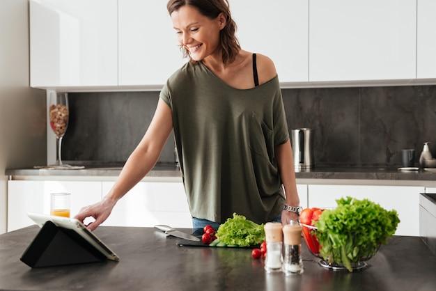 Femme casual souriante, debout près de la table avec des légumes dans la cuisine et à l'aide d'un ordinateur portable