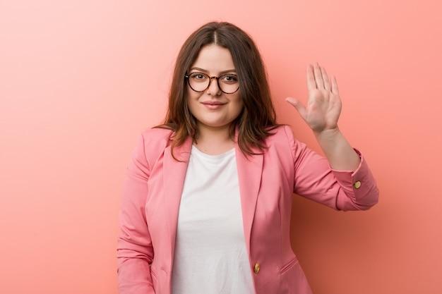 Femme caucasien de taille plus jeune entreprise souriant sourire montrant le numéro cinq avec les doigts.