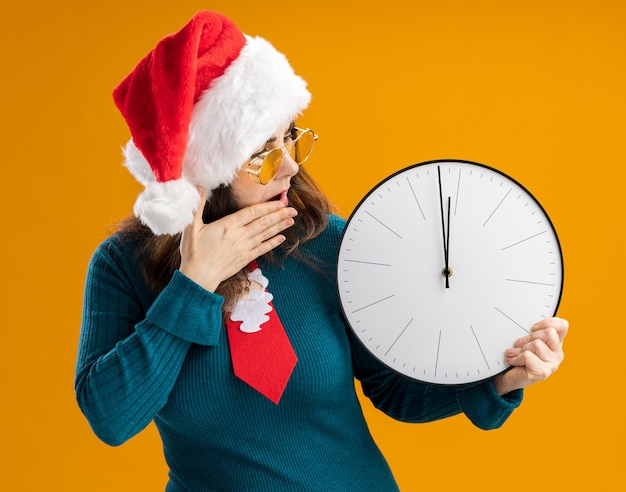 Une femme caucasienne adulte choquée dans des lunettes de soleil avec un chapeau de père noël et une cravate de père noël met la main sur la bouche tenant et regardant l'horloge isolée sur un mur orange avec espace de copie