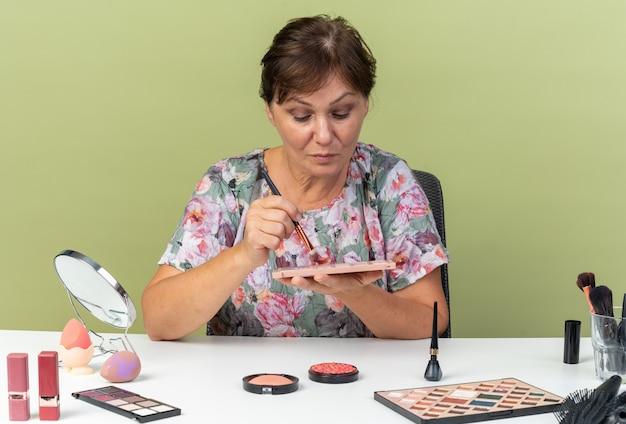 Femme caucasienne adulte confiante assise à table avec des outils de maquillage tenant un pinceau de maquillage et regardant la palette de fards à paupières