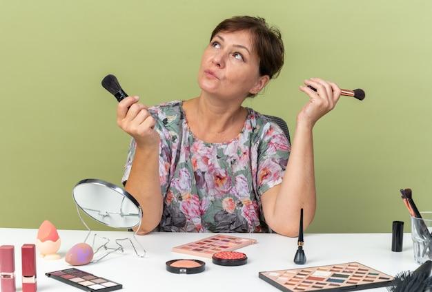 Femme caucasienne adulte confiante assise à table avec des outils de maquillage tenant des pinceaux de maquillage et regardant le côté isolé sur un mur vert olive avec espace de copie
