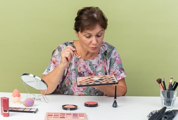 Femme caucasienne adulte confiante assise à table avec des outils de maquillage tenant et regardant la palette de fards à paupières et le pinceau de maquillage
