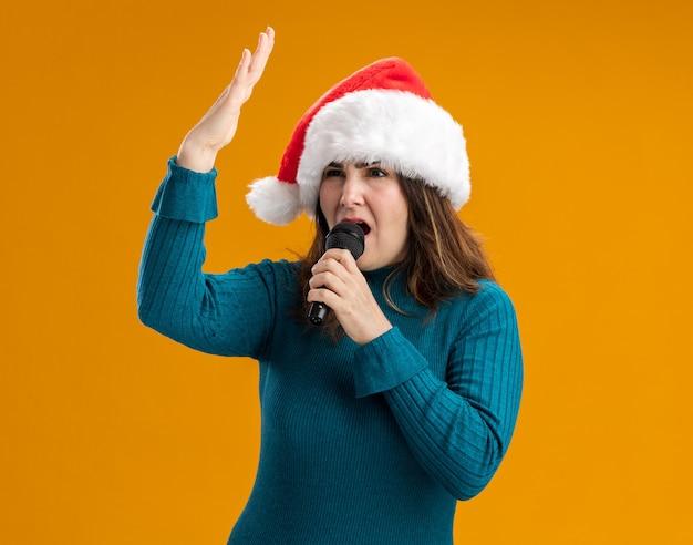 Une femme caucasienne adulte confiante avec un bonnet de noel tient un micro faisant semblant de chanter isolé sur un mur orange avec espace de copie