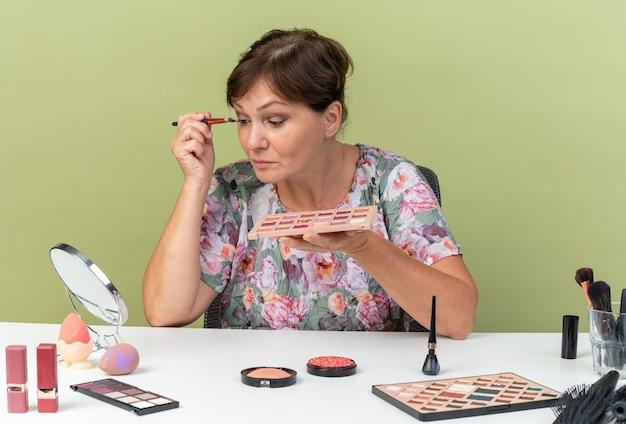 Femme caucasienne adulte impressionnée assise à table avec des outils de maquillage tenant une palette de fard à paupières et appliquant un fard à paupières avec un pinceau de maquillage