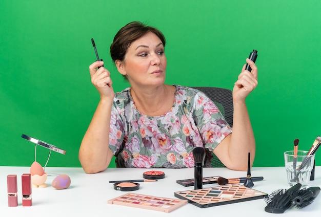 Femme caucasienne adulte impressionnée assise à table avec des outils de maquillage tenant et regardant le mascara isolé sur un mur vert avec espace pour copie