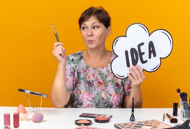 Femme caucasienne adulte surprise assise à table avec des outils de maquillage tenant une bulle d'idée et regardant un pinceau de maquillage