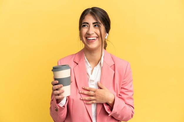 Femme caucasienne d'affaires isolée sur fond jaune souriant beaucoup