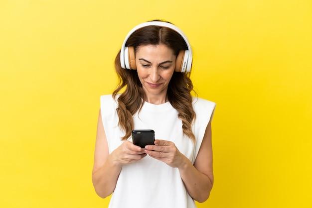 Femme caucasienne d'âge moyen isolée sur fond jaune, écoutant de la musique et regardant un mobile