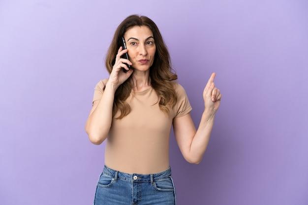 Femme caucasienne d'âge moyen utilisant un téléphone portable isolé sur fond violet montrant et levant un doigt en signe du meilleur