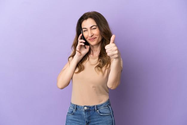 Femme caucasienne d'âge moyen utilisant un téléphone portable isolé sur fond violet avec le pouce levé parce que quelque chose de bien s'est produit