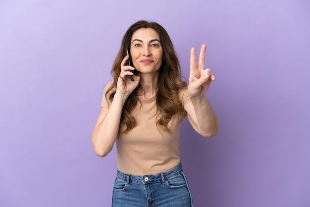 Femme caucasienne d'âge moyen utilisant un téléphone portable isolé sur fond violet souriant et montrant le signe de la victoire