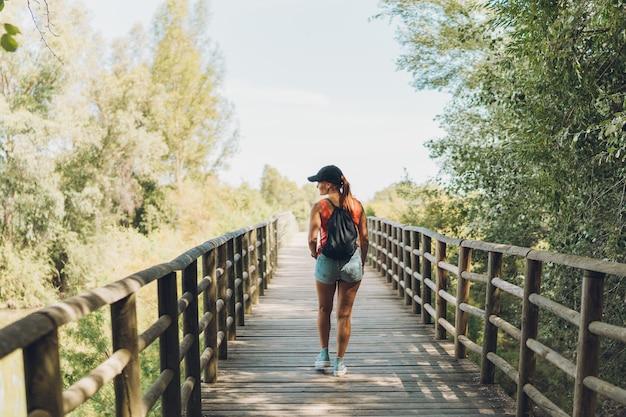 Femme caucasienne d'âge moyen en vêtements d'été marchant sur un pont sur un sentier rural.