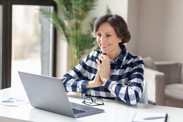 Une femme caucasienne âgée souriante et souriante suit un cours éducatif en ligne ou discute lors d'un appel vidéo sur un ordinateur portable depuis le bureau à domicile