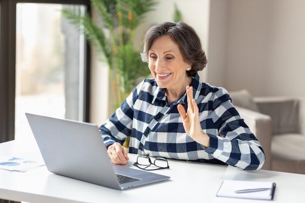 Une femme caucasienne âgée souriante suit un cours en ligne ou participe à une vidéoconférence sur un ordinateur portable depuis son bureau à domicile