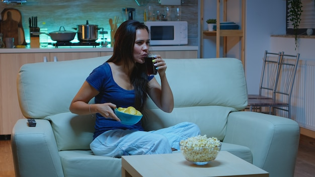 Femme caucasienne assise sur un canapé et regardant la télévision se détendre après le travail. dame seule à la maison amusée et excitée en pijama se reposant avec des collations et du jus, assise sur un canapé confortable dans un salon à aire ouverte.