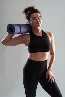 Une femme caucasienne athlétique pensive en vêtements de sport porte un tapis roulé et regarde calmement la caméra après s'être entraînée à l'intérieur. prise de vue en studio