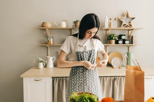 Femme caucasienne attache une préparation de tablier à la cuisson des aliments