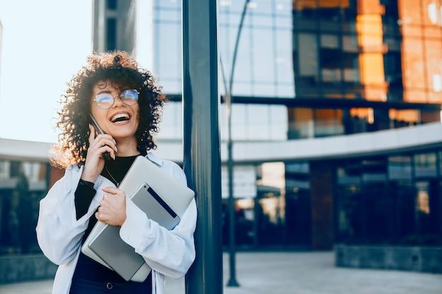 Femme caucasienne aux cheveux bouclés a une discussion d'affaires tout en tenant son ordinateur portable et en regardant à travers des lunettes