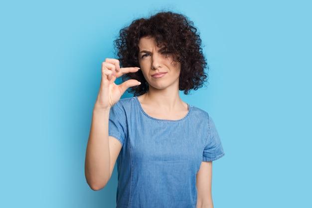 Femme caucasienne aux cheveux bouclés posant sur un mur bleu et faisant des gestes le petit signe