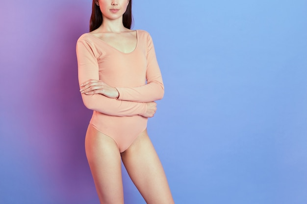Femme caucasienne aux cheveux noirs posant en body beige isolé sur un mur bleu avec néon rose, dame au corps parfait garde les bras croisés, fille aux longues jambes.