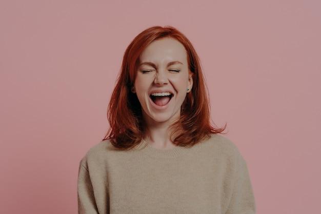 Femme caucasienne aux cheveux rouges ravie riant positivement, les yeux fermés, exprimant des émotions positives après avoir entendu une blague ou une anecdote hilarante, isolée sur fond rose. concept d'expressions de visage