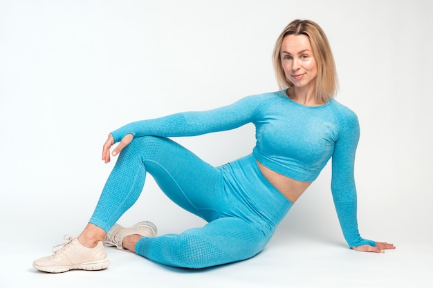 Femme caucasienne blonde réfléchie en vêtements de sport bleus regardant la caméra pensivement tout en se reposant après l'exercice du matin sur fond de mur blanc