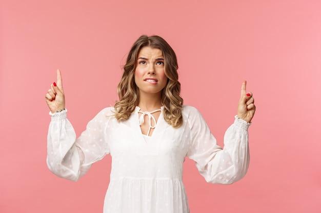 Femme caucasienne blonde sceptique et embarrassée en robe mignonne blanche, grimaçant, grincer des dents de voir quelque chose de dégoûtant, fronçant les sourcils douteux et pointant les doigts vers le haut d'une chose étrange, sur un mur rose