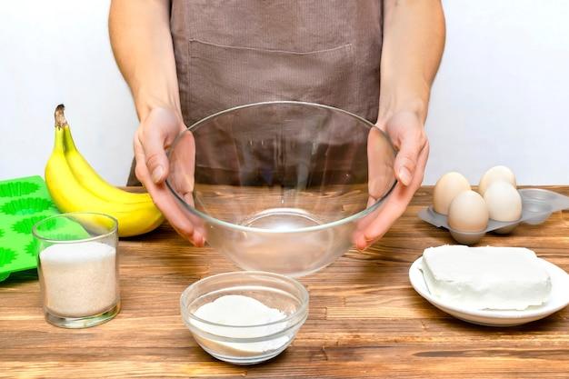 Femme caucasienne chef en tablier préparant des ingrédients pour faire des muffins à la banane au fromage cottage, des cupcakes, une casserole à la maison, cuisine, cuisine en ligne, instruction de recette