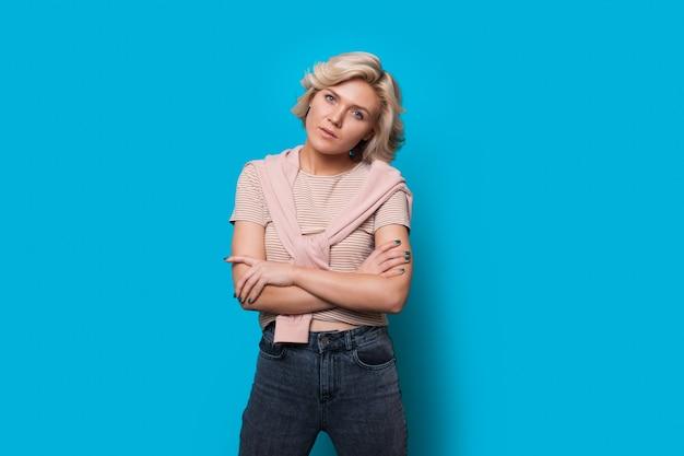 Femme caucasienne concentrée aux cheveux blonds pose avec les mains croisées sur un fond bleu