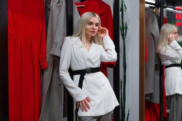Une femme caucasienne dans une boutique de mode choisit une robe. un styliste professionnel aide les clients à choisir des vêtements. saison vacances shopping remises vente fille européenne à pied centre commercial. mode de vie