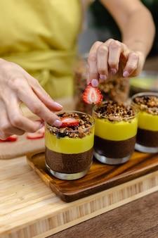 Femme caucasienne dans la cuisine fait des puddings de chia avec de la confiture de mangue. désert fait de lait d'amande, graines de chia, cacao, confiture de mangue et granola.