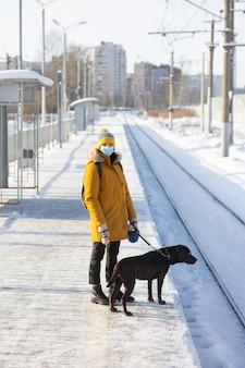 Femme caucasienne dans une veste jaune de masque médical avec un chien labrador retriever attendant un train
