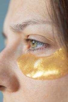 Une femme caucasienne ou européenne avec des taches dorées sous les yeux prend soin de sa peau en hydratant
