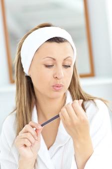 Femme caucasienne, faire ses ongles avec une lime à ongles