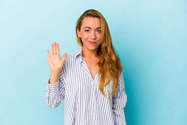 Femme caucasienne isolée sur fond bleu souriant gai montrant le numéro cinq avec les doigts.