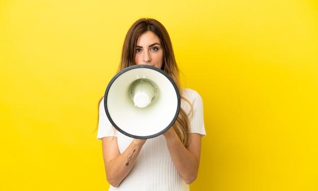 Femme caucasienne isolée sur fond jaune criant à travers un mégaphone pour annoncer quelque chose