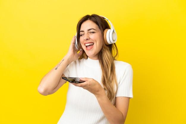 Femme caucasienne isolée sur fond jaune, écoutant de la musique avec un mobile et chantant