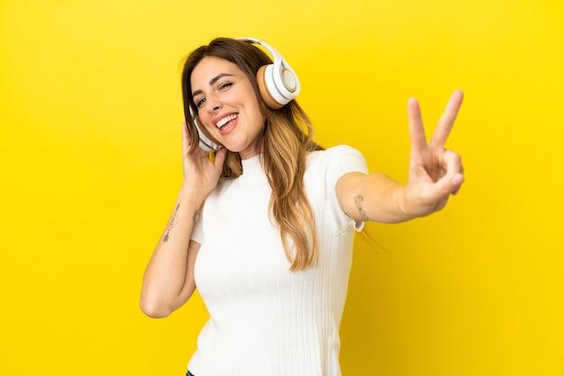 Femme caucasienne isolée sur fond jaune, écouter de la musique et chanter