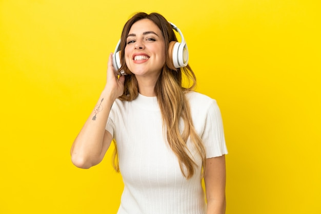 Femme caucasienne isolée sur fond jaune, écouter de la musique