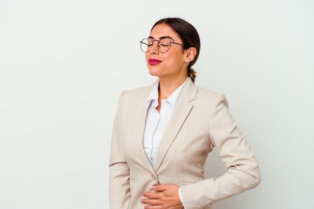 Femme caucasienne jeune entreprise isolée sur fond blanc touche le ventre, sourit doucement, concept de manger et de satisfaction.