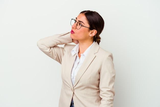 Femme caucasienne jeune entreprise isolée sur fond blanc, toucher l'arrière de la tête, penser et faire un choix.