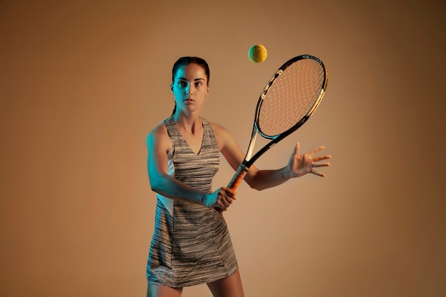 Une femme caucasienne jouant au tennis isolé sur fond marron en lumière mixte et néon. ajuster la jeune joueuse en mouvement ou en action pendant le jeu de sport. concept de mouvement, sport, mode de vie sain.