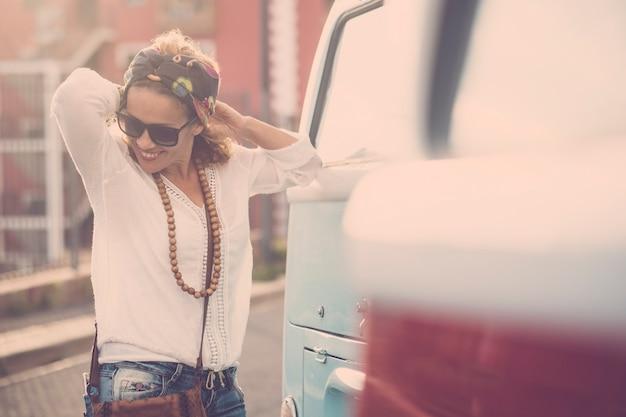 Une femme caucasienne joyeuse et heureuse profite de l'activité de loisirs en plein air au coucher du soleil près de deux vieux fourgons vintage prêts à voyager et à profiter du style de vie de l'errance avec des vêtements et des accessoires de mode