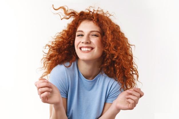 Femme caucasienne joyeuse et insouciante dansant de joie et de joie, levant les mains en souriant optimiste, s'amusant, célébrant les vacances d'été, mur blanc