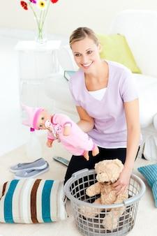 Femme caucasienne joyeuse, mettre des jouets dans un panier