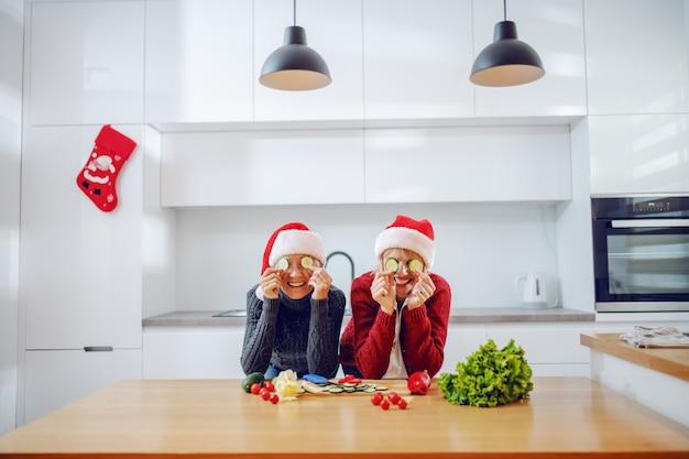 Femme caucasienne ludique et sa mère tenant des tranches de concombre devant leurs yeux tout en se penchant sur le comptoir de la cuisine. les deux ont des chapeaux de père noël sur la tête. réveillon de nouvel an.